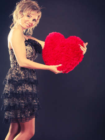 afecto: Woman mid age blonde female elegant evening dress holding big red heart love symbol studio shot on black. Valentines day happiness concept