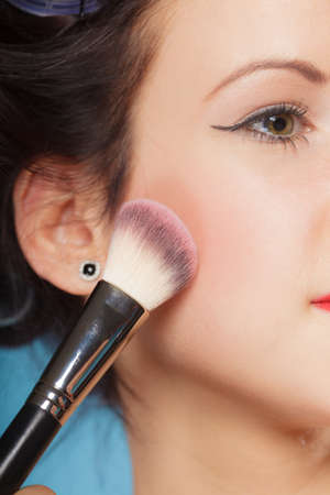 cheekbones: Cosmetic beauty procedures and makeover concept. Woman applying makeup blusher with brush. Girl gets blush on cheekbones closeup part of face