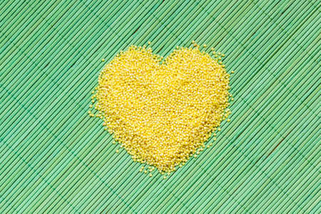 protein crops: Dieting healthcare concept. Millet groats heart shaped on green straw mat surface. Healthy food non gluten grain.