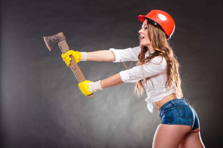axe girl: Sexy alluring woman wearing helmet hitting with axe chopper. Strong girl feminist working in man profession. Independent female.