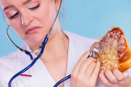 fattening: Disgusted dietitian nutritionist checking examine sweet roll bun with stethoscope. Woman with fattening junk food. Bad unhealthy eating nutrition concept. Stock Photo