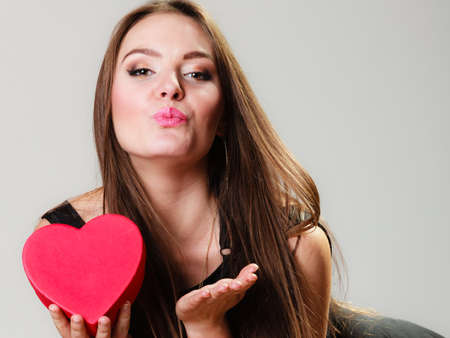 anniversary sexy: Happiness, valentines day and love concept. Lovely elegant woman with red heart-shaped gift box blowing a kiss on gray
