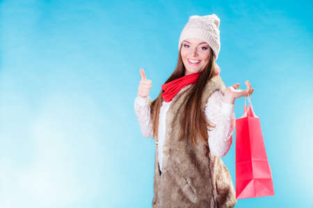 Winter woman in warm clothing with red paper shopping bag showing thumb up on blue. Girl buying. Sale, consumerism and retail.