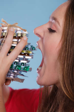 swallowing: Woman taking pills. Girl female eating stack of tablets. Drug addict and health care concept. Overdose. Stock Photo