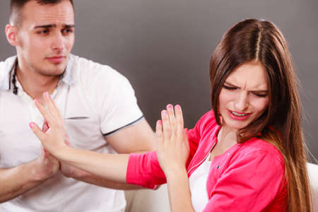 apology: Husband apologizing wife. Upset, angry, mad woman refuses apology pushing him away. Boyfriend trying to convince girlfriend. Man asking for forgivness. Conflicted couple. Relationship problem. Stock Photo