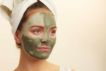 mud woman: Skin care. Woman face with green clay mud mask. Girl taking care of oily complexion. Beauty treatment. Stock Photo
