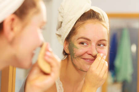 purifying: Woman removing facial dried clay mud mask with sponge in bathroom in front of mirror. Skin care. Girl taking care of her complexion. Beauty spa treatment. Stock Photo