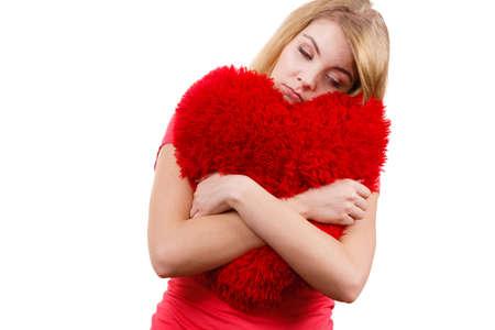 heartsick: Woman blonde sad unhappy girl hugging red heart shaped big pillow studio shot on white. Heartbroken young female. Stock Photo