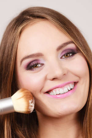 gorgeous girl: Woman applying anti-shine loose powder with brush to her face. Pretty gorgeous girl beautifying. Fashion and makeup Stock Photo
