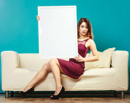 woman holding sign: Advertisement concept. Elegant young woman sitting on sofa holding blank presentation board. Girl showing banner sign billboard copy space for text.