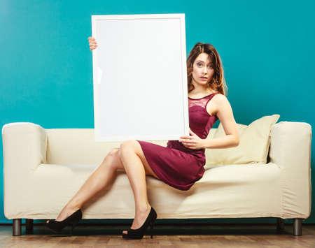 mujer sentada: Concepto de Publicidad. Mujer joven elegante que se sienta en el sofá que sostiene un tablero de presentación en blanco. Muchacha que muestra la muestra de la bandera cartelera copia espacio para el texto. Foto de archivo