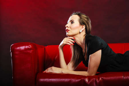 lady in red: Fashion beauty and elegance concept. Woman retro style face profile. Elegant lady red lips nails lying on sofa