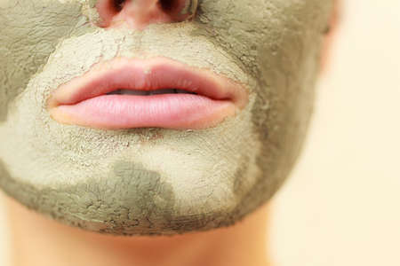mud girl: Skin care. Woman face with green clay mud mask close up. Girl taking care of oily complexion. Beauty treatment.