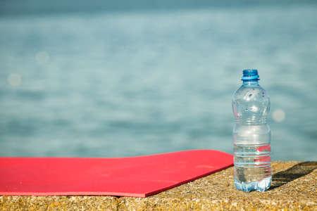 Leichtschaum Yoga-Matte und Wasser Plastikflasche im Freien auf Meer. Sportausrüstung. Aktiver Lebensstil