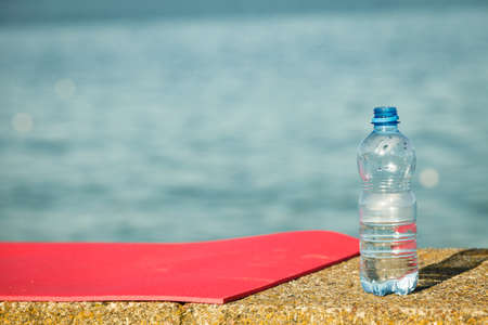 yoga outside: Lightweight foam yoga mat and water plastic bottle outdoor on sea shore. Sport equipment. Active lifestyle