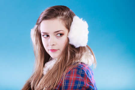 earmuff: Young woman wearing fluffy white earmuff. Teenage in cold time. Stock Photo