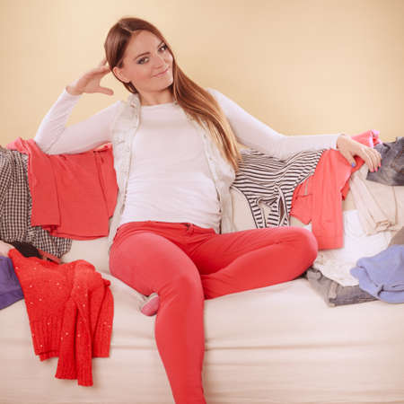 habitacion desordenada: Happy woman sitting on sofa couch in messy room. Girl surrounded by stack of clothes. Disorder and mess at home.