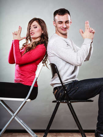 loving couples: Happy couple having fun and fooling around pretending their hands fingers are guns. Joyful man and woman have nice time sitting back to back. Good relationship.