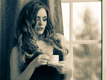 energizing: Sensual seductive woman in lingerie drinking cup of coffee by curtain and french door window at home. Young girl with hot energizing beverage stay awake. Caffeine energy. Black and white. Stock Photo