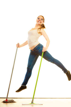 mops: Cleanup housework concept. Funny cleaning lady young woman mopping floor, holding two mops new and old jumping white background Stock Photo