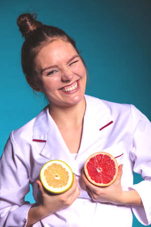 dietitian: Happy dietitian nutritionist holding grapefruit having fun. Woman promoting healthy food fruit. Right eating nutrition and slimming concept.
