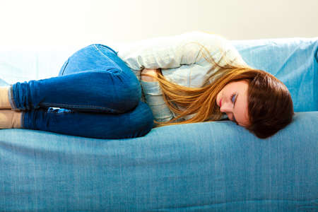 divorce: Loneliness negative emotion concept. Young sad stressed woman lying on couch at home