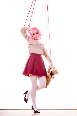 marionette: Mental disorder concept. Young woman girl stylized like marionette puppet on string with teddy bear toy isolated on white background