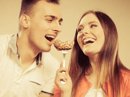 caloric: Smiling woman feeding happy man with cake. Wife and husband eating caloric food. Instagram filtered.