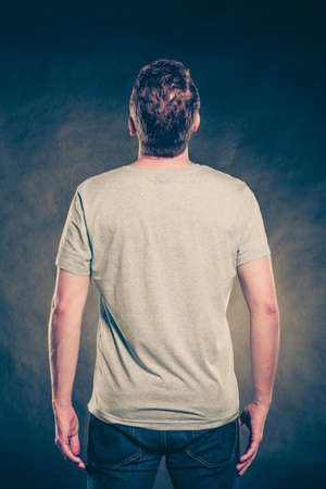 Back rear view of fashionable man in blank shirt with empty copy space. Guy in studio on black. Casual fashion advertisement.