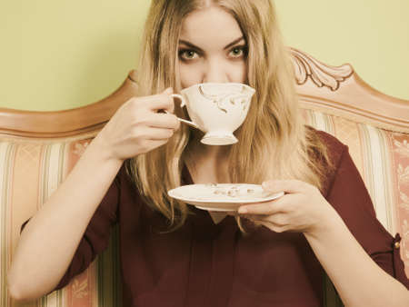 energizing: Fashionable woman drinking cup of coffee sitting on vintage sofa. Young girl with hot energizing beverage stay awake. Caffeine energy. Sepia.