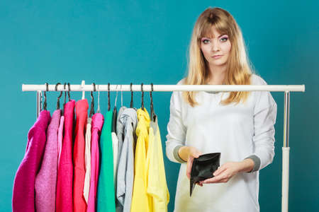 Pretty woman with empty wallet want clothing from wardrobe. Young undecided shopper girl spend all money for clothes. Shopaholic concept. Banco de Imagens