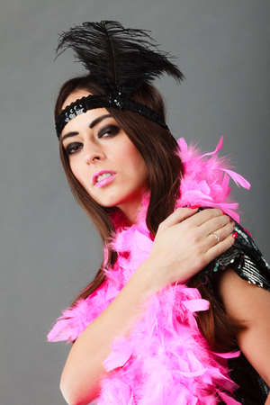 flapper: Retro flapper woman on carnival time. Young female pink plume black feather on head and sequin glossy evening dress