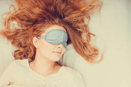 taking nap: Tired woman sleeping in bed wearing blindfold sleep mask. Young girl taking nap.