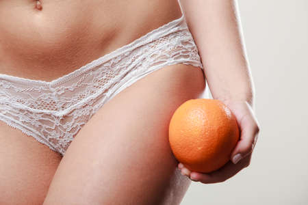aspects: Absence of cellulite. Part body of slim fit girl holding orange next to the bottom buttocks. Woman wearing white lacy lingerie. Diet aspects. Stock Photo