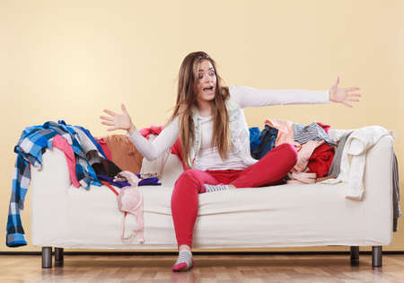 Woman sitting on sofa couch in messy room. Girl surrounded by stack of clothes. Disorder and mess at home.