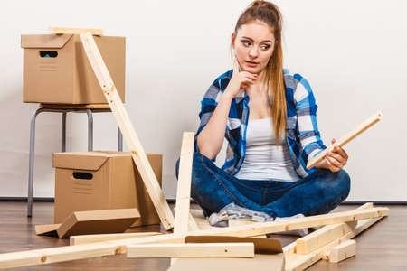self assembly: Worried woman moving into new apartment house assembling furniture. Young girl arranging interior and unpacking boxes.