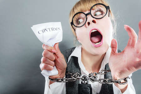 office slave: Business and stress concept. Furious businesswoman in glasses with chained hands holding contract grunge background unusual angle view