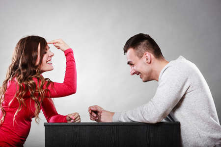mocking: Woman gesturing with finger on her head sitting in front of man. Are you crazy? Girl mocking laughing at man. Stock Photo