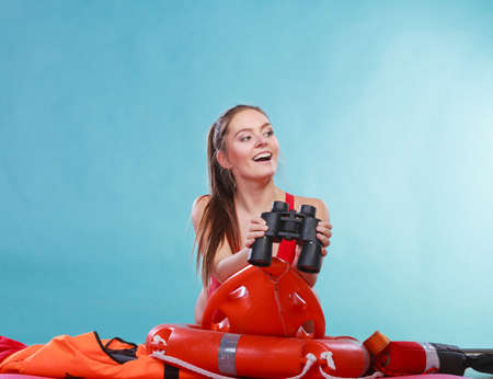 float tube: Lifeguard with rescue tube buoy. Woman supervising swimming pool water looking through binoculars. Accident prevention and rescue.
