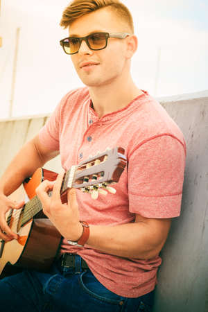 a guitarist boy playing guitar: Performance and show on fresh air. Young fashionable man wearing sunglasses playing classic guitar outdoor. Summer time. Stock Photo
