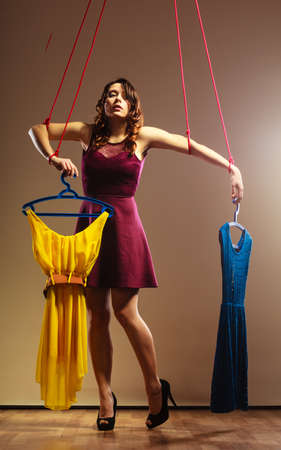 marionette: Shopaholic fashion addiction concept. Addicted to shopping woman, girl marionette puppet with clothes on string, buying disorder.
