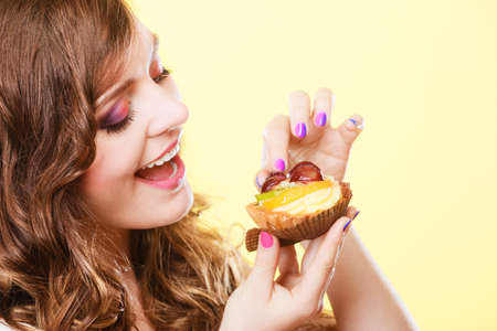 indulging: Sweetness and happiness concept. Closeup cute woman curly hair eating fruit cake cupcake face profile yellow background