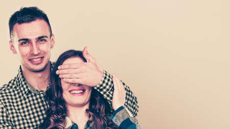 surprised: El hombre que cubre los ojos de la mujer para la sorpresa. feliz pareja lúdica sonriendo y divirtiéndose.
