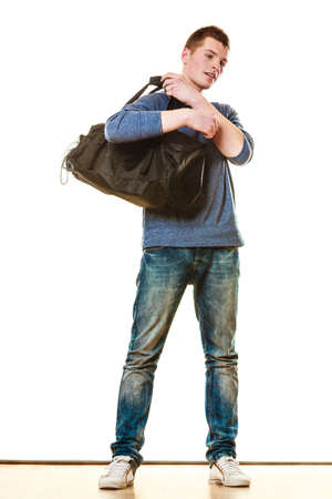 handbag model: Young fashionable man teen boy in full length casual style blue jeans holding black bag isolated on white