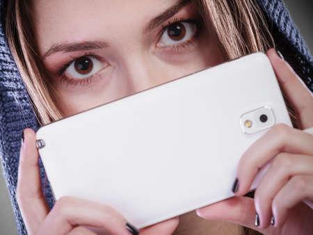 big behind: Young woman hiding behind phone. Using technology. Big eyes Stock Photo