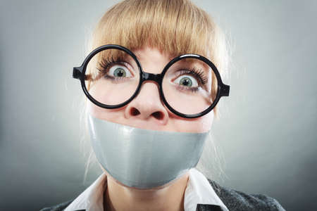 Scared woman with mouth taped shut. Afraid young girl with duct tape on lips. Censorship and freedom of speech concept.