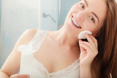 removing: Woman removing makeup with cotton swab pad. Young girl taking care of skin. Skincare concept. Stock Photo