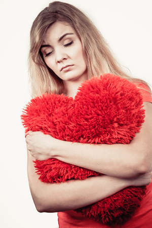 heartsick: Woman blonde sad unhappy girl hugging red heart shaped big pillow studio shot on white. Heartbroken young female. Stock Photo