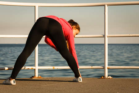 stretch out: Woman jogger athletic female taking break from running to stretch out on pier by seaside back view Stock Photo