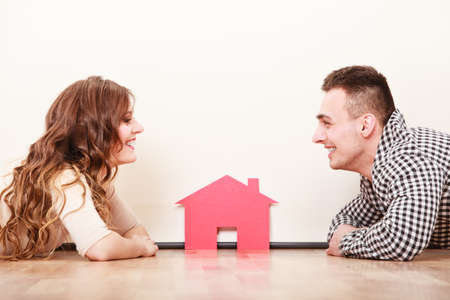 husband: Young couple holding paper house and key. Husband and wife dreaming about new home. Housing and real estate concept. Stock Photo